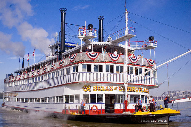 Belle of Louisville paddle boat, steamboat, on the Ohio River at Louisville, KY, decked out with red, white & blue American flag-like swag